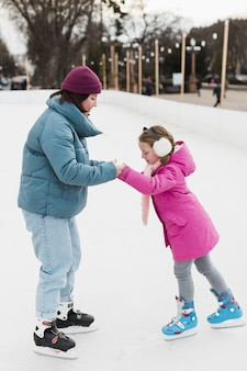 Daughter and mom ice skating together
