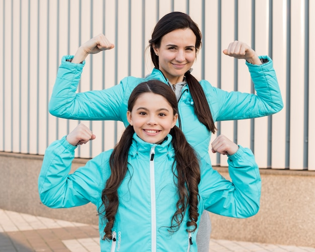 Daughter and mom showing muscles