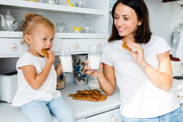 Daughter and mother drinking milk and eating cookies