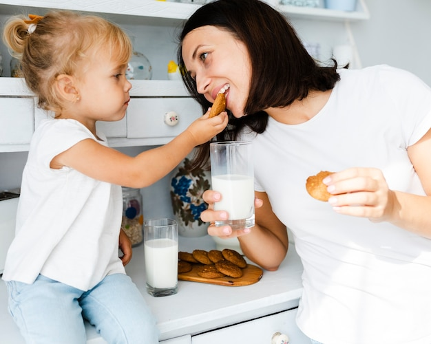 Daughter and mother eating cookies