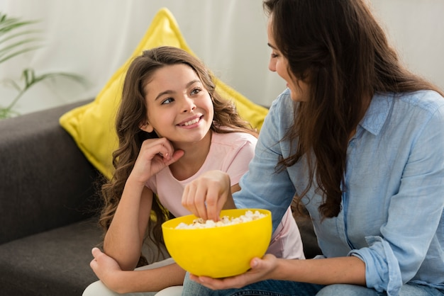 Daughter and mother eating popcorn together