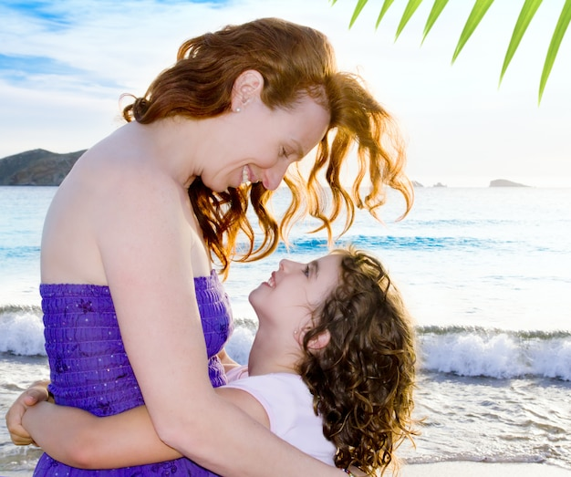 Daughter and mother hug on the ibiza beach