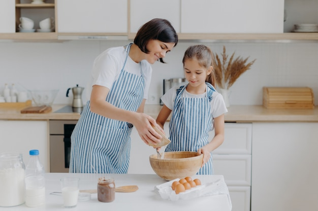 Daughter and mother love cooking, dressed in striped aprons, prepare delicious dinner, use different ingredients, have kitchen routine, stand at home.