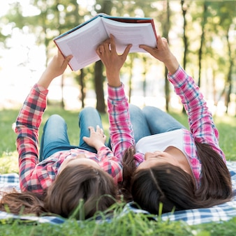 Daughter and mother lying on blanket during reading book in park