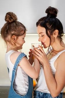 Daughter and mother sharing orange juice together