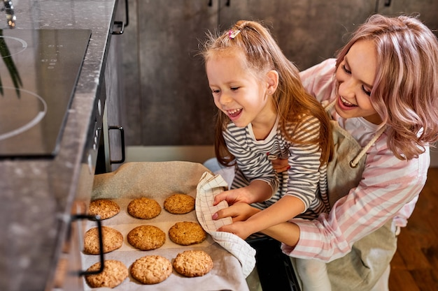 Daughter and mother taking out tray of baked cookies from oven in kitchen