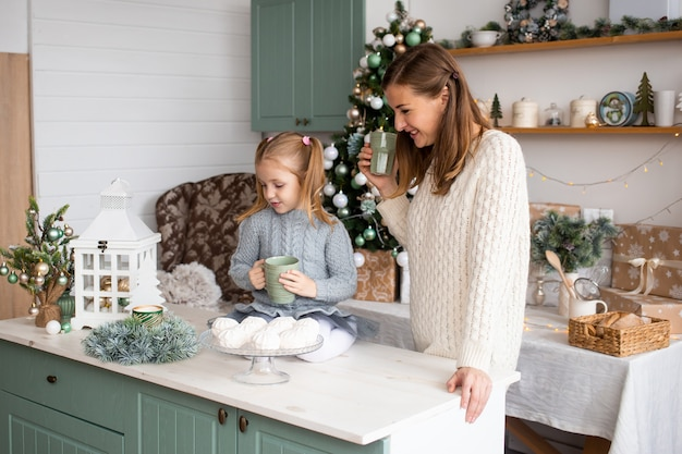Daughter and mother with tea cups in christmas kitchen at home.
