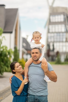 Daughter on neck. strong father with daughter on neck walking with beautiful wife and his girl