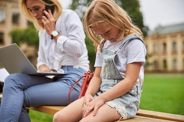 그들은 나무 벤치에 공원에 앉아있는 동안 바쁜 화가 어머니의 관심을 필요로하는 딸