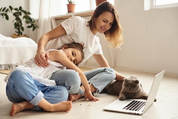 딸이 엄마와 고양이와 함께 재생하는 동안 엄마는 컴퓨터에서 작동합니다.