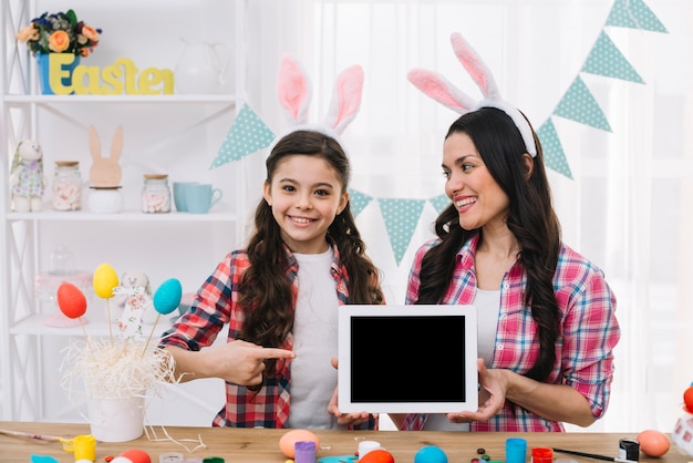 Daughter pointing finger to the digital tablet hold by her mother on easter day