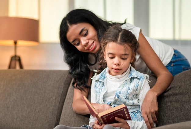 Daughter reading with mom support