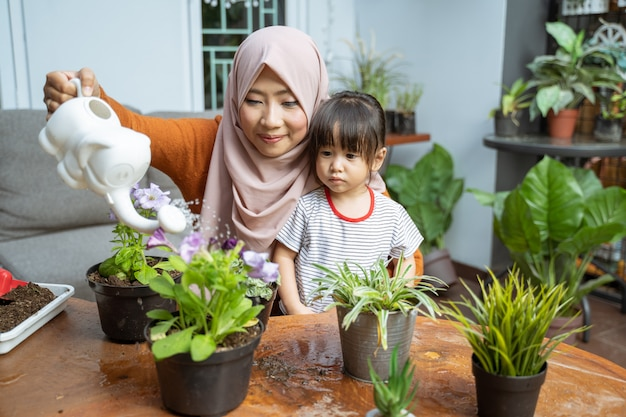 Daughter sees her mother holding a watering can while watering plants