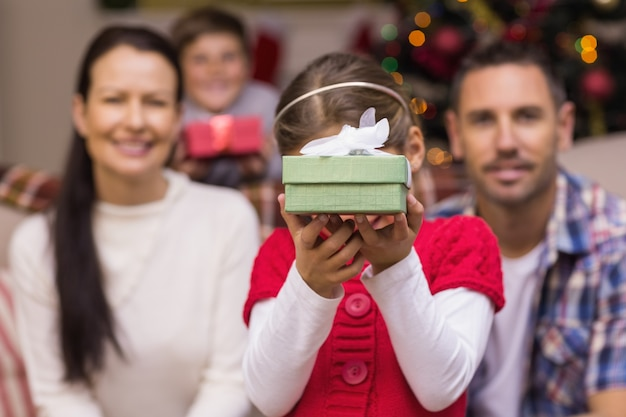 Daughter showing a gift with her family behind
