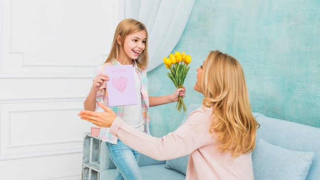 Daughter showing gifts flowers and mother`s day postcard for mom