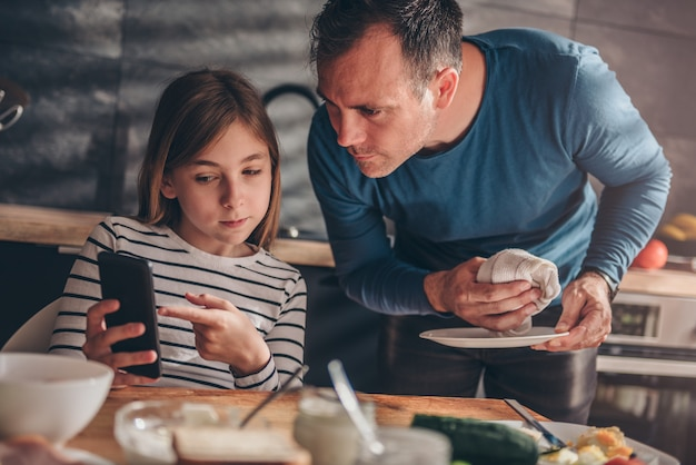Daughter showing text message to a father