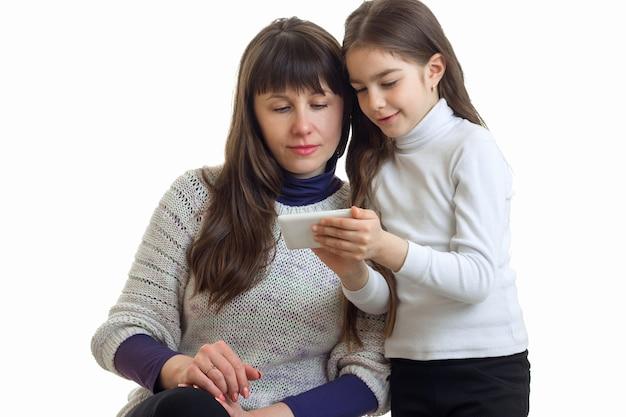 Дочь показывает маме фотографии на своем телефоне, изолированные на белом