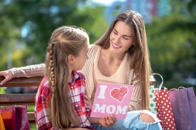 Дочь сидит с мамой на скамейке в парке, показывая свою открытку