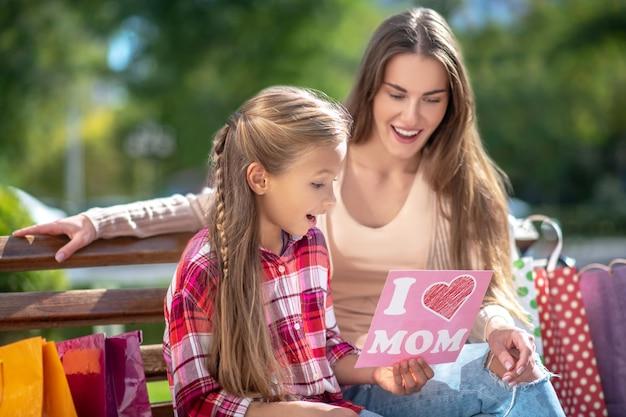 Дочь сидит со своей удивленной мамой на скамейке в парке, показывая свою открытку