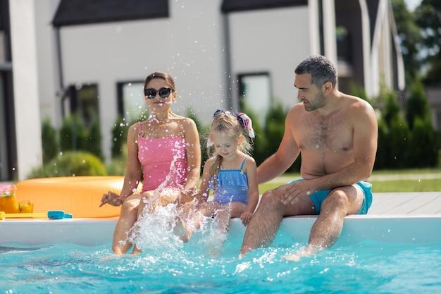 Дочь брызгает водой. маленькая забавная дочь брызгает водой, сидя у бассейна с родителями