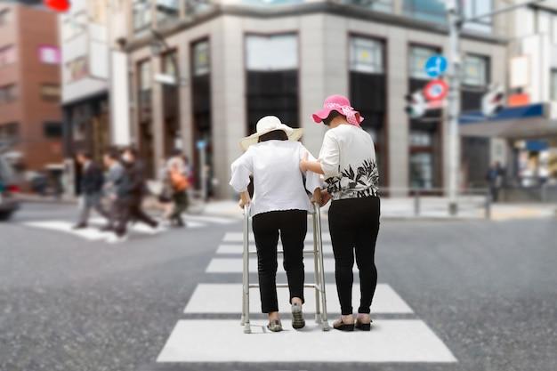 娘は強い日光の下で通りを歩いている年配の女性の世話をします。