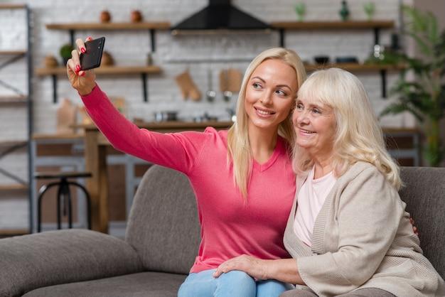 그녀의 어머니와 함께 selfie를 복용하는 딸