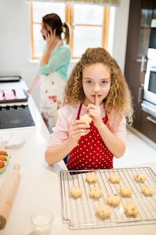 Daughter taking cookies secretly while mother talking on mobile
