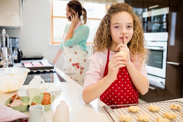 娘の母親が携帯電話で話しながら、密かにクッキーを取ります