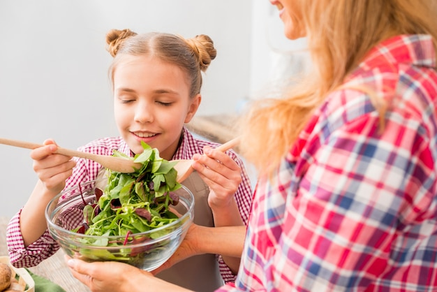 Daughter taking the smell of fresh leafy salad in the bowl hold by her mother