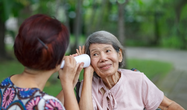 Daughter talking to hearing impaired elderly woman , using paper tube
