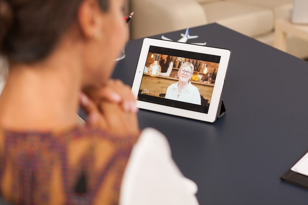 Daughter talking with her mother during a video call on tablet computer.