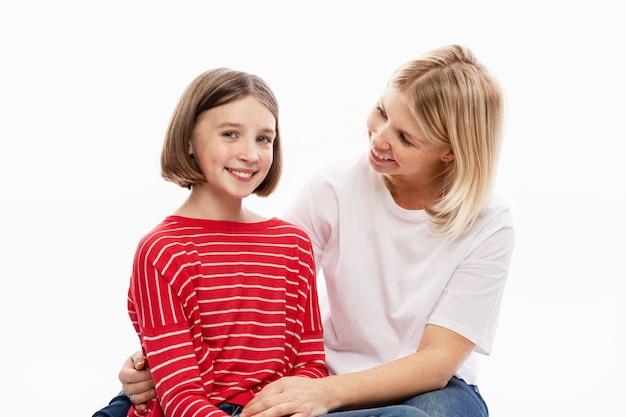 Дочь-подросток и мама смеются и обнимаются. любовь и поддержка в семейных отношениях. белая стена. пространство для текста.