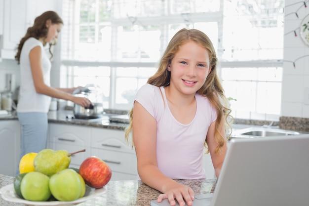 キッチンで背景に母親とラップトップを使用して娘を食べる