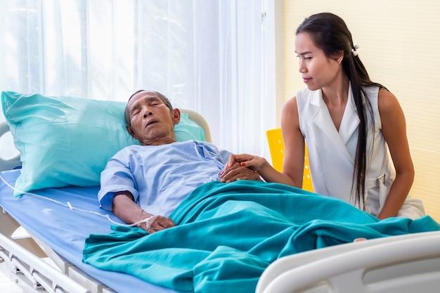 病院で年配の男性患者を訪問して慰める娘。