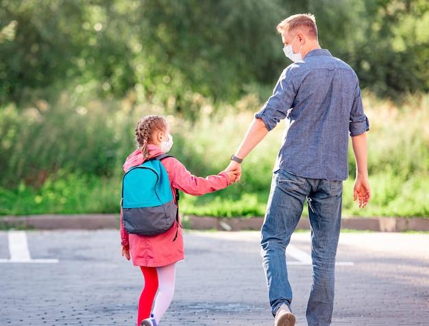 コロナウイルスのパンデミック中に放課後父親と手をつないで歩く娘