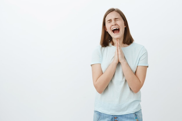 Daughter whining and crying heart out so dad buy new smartphone holding hands in pray near body yelling out loud with closed eyes trying persuade father to help her and present gift