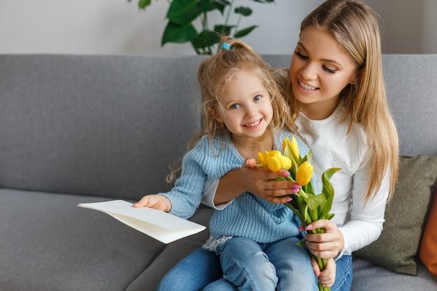 花の花束を持つ娘、はがきはお母さんを祝福します