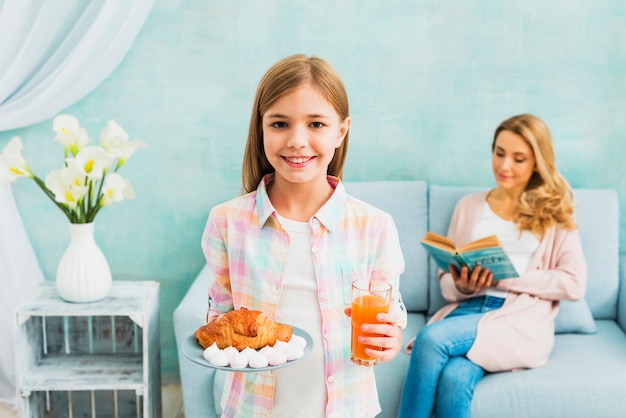 Daughter with breakfast smiling near mother