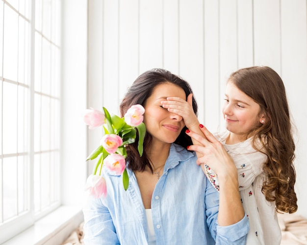Daughter with flowers covering eyes of mother