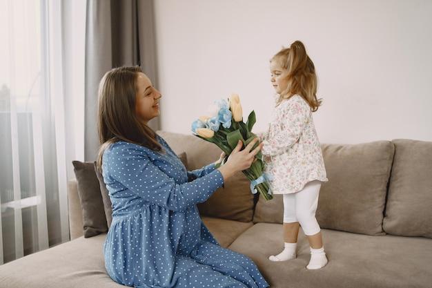 花を持つ娘。ソファの上の妊娠中のお母さん。明るい服を着た母と娘。