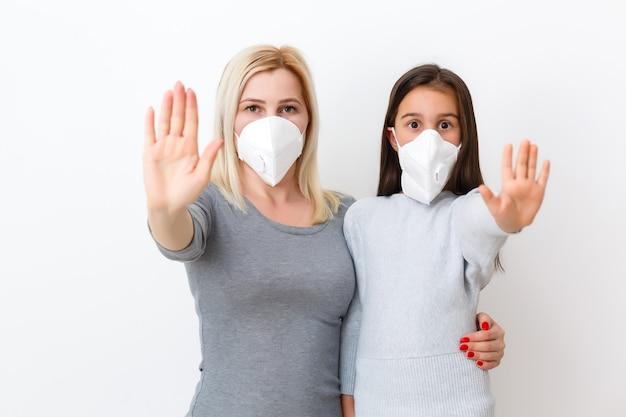 サージカルマスクでお母さんと娘。フェイスマスクffp1の子供を持つ家族。公共の混雑した場所でのウイルスと病気の保護。母と娘のベッドルームは保護マスク、ヘルスケアを着用します