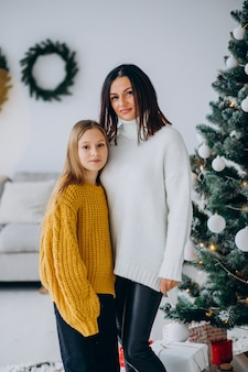 Daughter with mother by the christmas tree