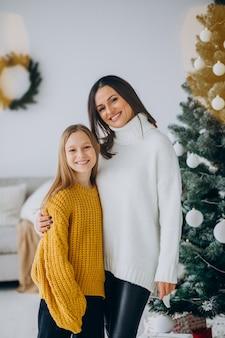 Figlia con la madre dall'albero di natale