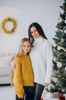 クリスマスツリーのそばで母親と娘