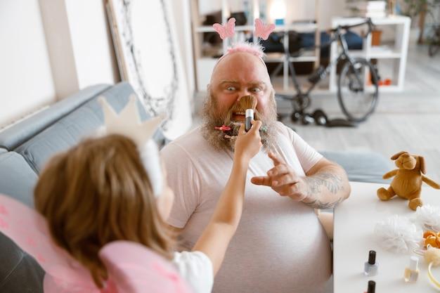 Дочь с короной принцессы наносит пудру на нос шокированному отцу в гостиной
