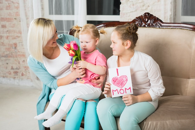 Daughters presenting gifts for mother
