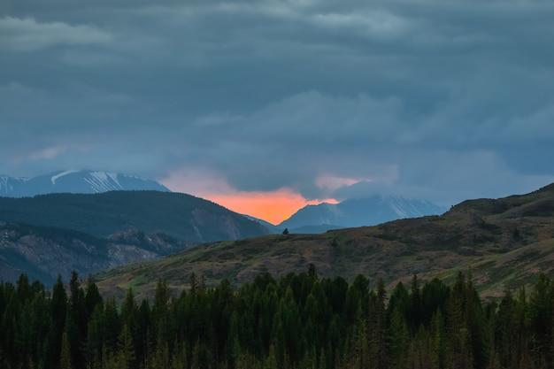 山の夜明け。夕日や日の出のカラフルな自然の風景。オレンジ色の夜明けの空を背景に木々と山のシルエットの雰囲気のある風景。
