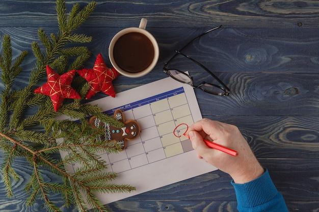 月の25日目、朝のコーヒーカップと職場の背景にカレンダー。新年のコンセプト。テキスト用の空きスペース