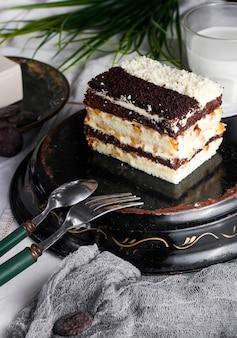茶色と白のケーキのクランブルで飾られたクリームとクルミの昼と夜のケーキ