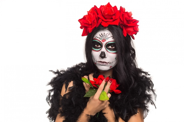 Day of the dead. halloween. young woman in day of the dead mask skull face art and rose. isolated on white. closeup.